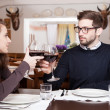 Smiling young man clinking glasses with his girlfriend while at dinner — Stock Photo