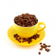 Yellow cup with saucer full of coffee beans — Stock Photo
