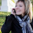A charming young woman in autumn park talking on the phone — Stock Photo