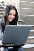 Charmiga brunett med en bärbar dator — Stockfoto