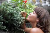 Charming young woman feeling the smell of flower — Stock Photo