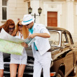 Young tourists with a road map against retro car — Stock Photo #26355249