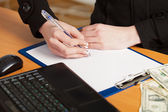 Person's hand signing an important document — Stock Photo