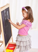 A little girl wrote in chalk on the graphite board. — Stock Photo