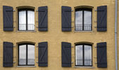 Four windows on the frontage of a house — Stock Photo