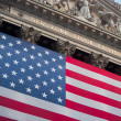 An American flag hangs on the front of the New York Stock Exchange building - Stock Photo