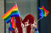 Hands waving gay flags — Stock Photo