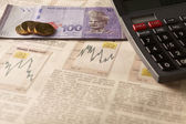 Newspaper stock market with calculator and money — Stock Photo