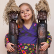 图库照片: Little girl with two ethnic dolls