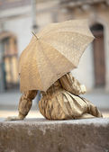 Live statue under umbrella — Stock Photo