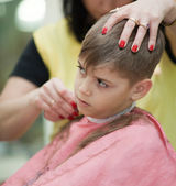 Cute young boy getting haircut — Stock Photo