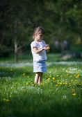 Little girl exploring dandelion — Stock Photo