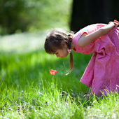 маленькая девочка нюхает цветок — Стоковое фото