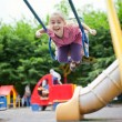 Girl swinging and laughing — Stock Photo