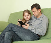 Daughter and father using e-book — Stock Photo
