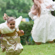 Two little beautiful girls jumping in a park — Stock Photo