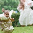 Stock Photo: Two little beautiful girls jumping in a park