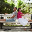 Happy couple sitting on bench in the park — Stockfoto