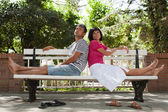 Happy couple sitting on bench in the park — Stock Photo