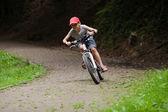 Boy racing on bike through green park — Stockfoto