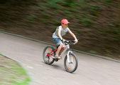Boy racing on bike through park — Stock Photo