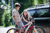 Young boy and girl taking a break from bicycling — Stock Photo
