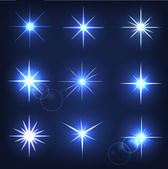 Set forms of sparks. Shining star on a blue background — Stock Vector