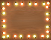 Christmas lights on wooden background, frame with garlands, hori — Stock Vector
