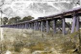 Old wooden Australian railway bridge with grunge textured filter — Stock Photo