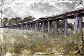 Old wooden Australian railway bridge with grunge textured filter — Stock Photo