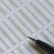 Ballpoint pen on financial figures — Stock Photo