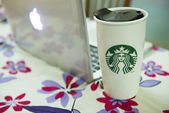 A tall Starbucks coffee in front of a laptop computer. — Stock Photo