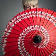 Girl Peeking Over Red Parasol — Stock Photo