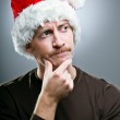 Man Wearing Santa Hat Thinking Of What Gifts To Give — Stock Photo