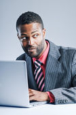 Young African American Businessman Being Sneaky On Laptop — Stock Photo