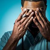 Médico afroamericano agotado frotando los ojos — Foto de Stock