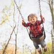 Toddler Swinging In Fall — Stock Photo #24998413