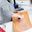 Woman washes cutting board in kitchen sink — Stock Photo