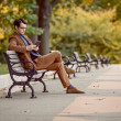Stock Photo: MRelaxing In Park Reading E-Reader
