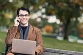Positive Young Man Multi-Tasking In The Park — Stock Photo