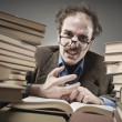 Angry professor rounded with stacks of books — Stock Photo