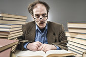 Young professor rounded with stacks of books — Stock Photo