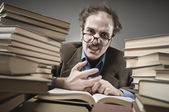 Angry professor rounded with stacks of books — Stock fotografie