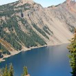 Slope of Crater Lake overgrow with trees — Stock Photo