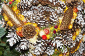 Christmas wreath with pine cones and flowers — Stock Photo