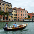 Stock Photo: VENICE - AUGUST 25. two men on motor boat floating on Gran