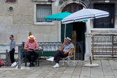 VENICE August 25. Gondoliers on vacation, sitting under umbrella — Stock Photo