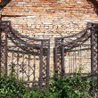 Old iron gates on a brick masonry — Stock Photo