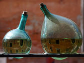 Two green bottles with reflection Venetian canals, Venice, Italy — Zdjęcie stockowe