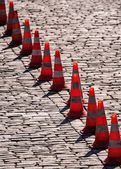 Road safety cones on a cobblestone street — Stock Photo